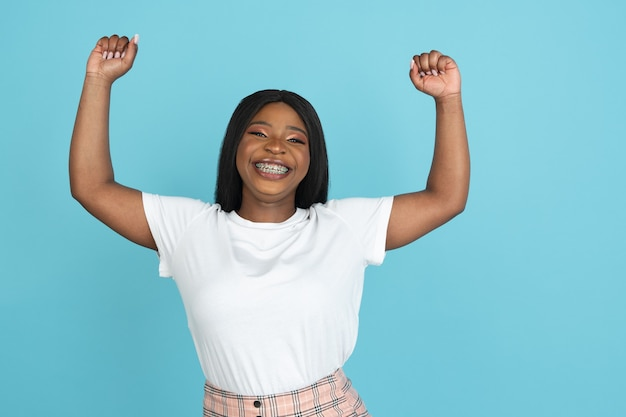 Giovane donna felice isolata sulla parete blu dello studio