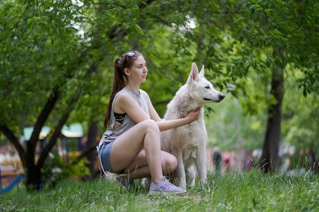 공원에서 그녀의 강아지와 조깅하는 행복 한 젊은 여자.