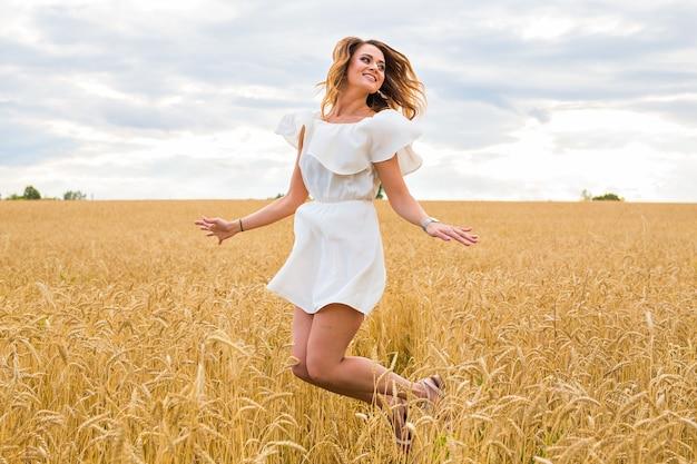 幸せな若い女性がフィールドにジャンプします。