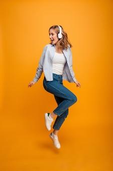 Счастливая молодая женщина прыгает слушать музыку