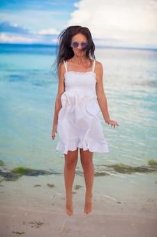 Счастливая молодая женщина прыгает возле воды на пляже