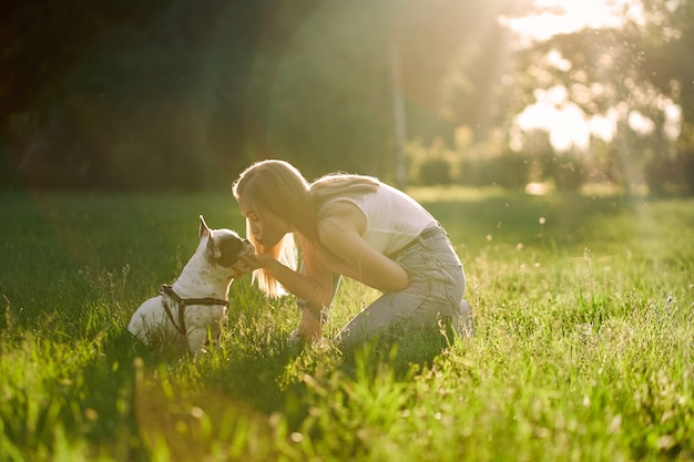 Happy young woman kissing french bulldog in park