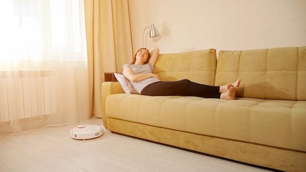 幸せな若い女性は白い丸い自動ロボット掃除機がリビングルームの木製の床をフーバーしながら枕と快適なソファに横たわっています