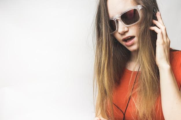 Счастливый молодая женщина слушает, длинные волосы, прохладные солнцезащитные очки. женщина в наушниках и очках