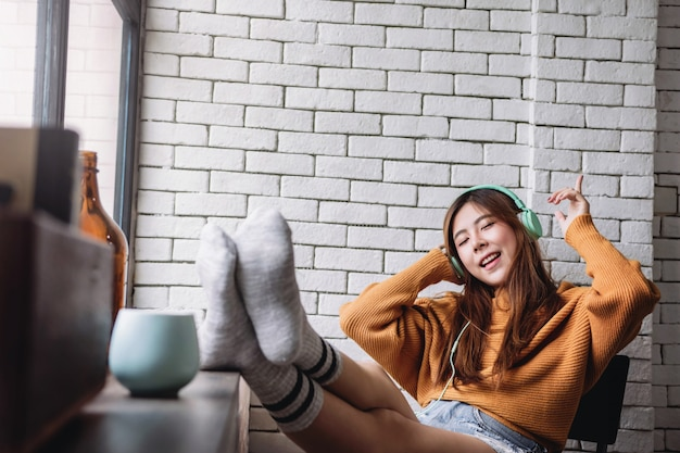Happy young woman listening music from headphone in cozy house, happiness moment