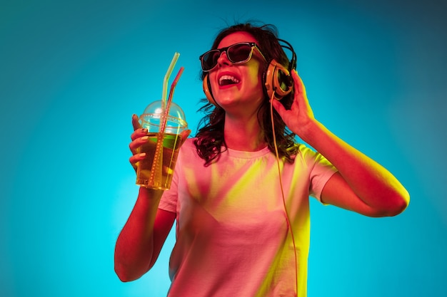 Happy young woman listening to the music and smiling over trendy blue neon