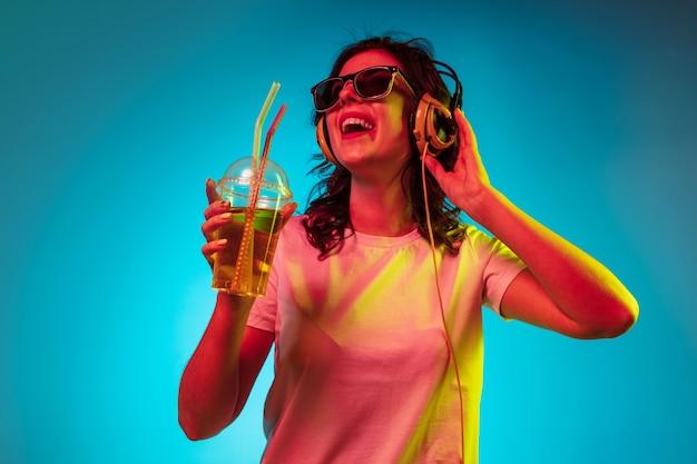 Giovane donna felice che ascolta la musica e che sorride sopra il neon blu alla moda