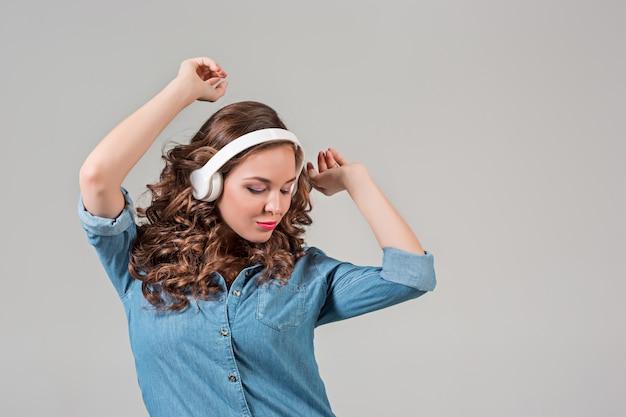 Musica d'ascolto della giovane donna felice con le cuffie. ritratto isolato su muro grigio