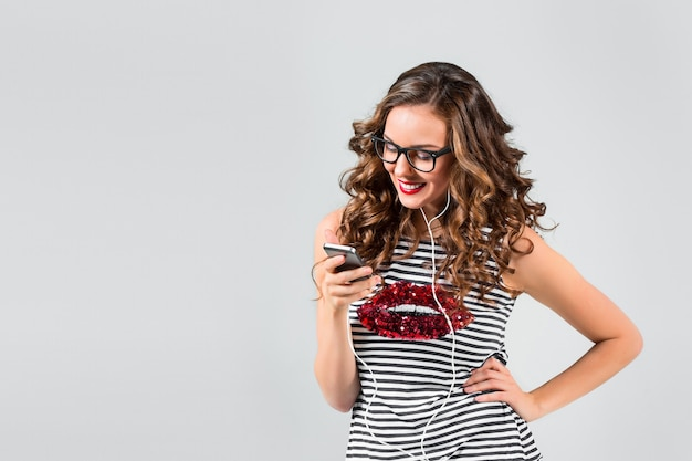 Музыка счастливой молодой женщины слушая с наушниками. изолированный портрет на серой стене