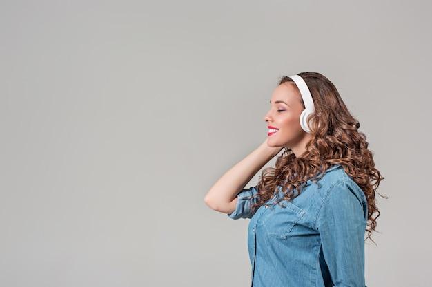 행복 한 젊은 여자 헤드폰으로 듣는 음악. 회색 벽에 고립 된 초상화
