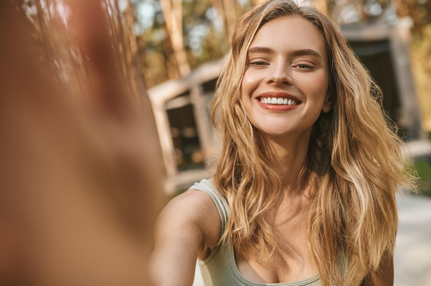 Счастливая молодая женщина, смотрящая в камеру