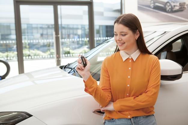 Счастливая молодая женщина смотрит на ключ от машины в руке, опираясь на свой недавно купленный автомобиль