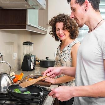 프라이팬에 브로콜리를 요리하는 그녀의 남편을보고 행복 한 젊은 여자