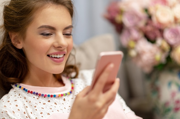 自宅でスマートフォンを見ている幸せな若い女性。女性はスマートフォンでメッセージを入力します。