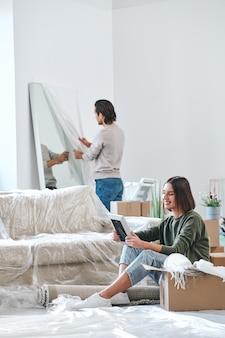 壁の前に鏡を開梱する夫の背景に床に座ってフレームで写真を見て幸せな若い女性