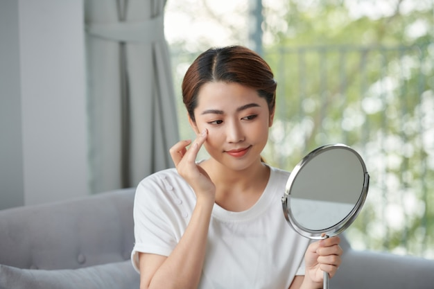 鏡を見ている幸せな若い女性
