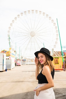 Happy young woman looking over shoulder with her hand in pocket at amusement park