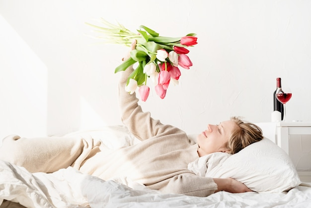 Happy young woman lying in the bed wearing pajamas holding tulip flowers bouquet