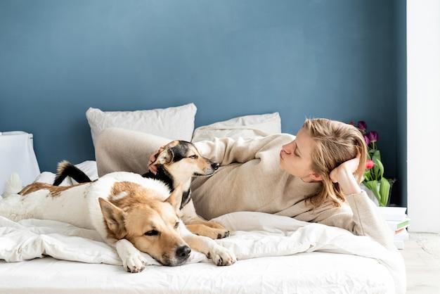 彼女の犬、青い壁の背景とベッドで横になっている幸せな若い女性