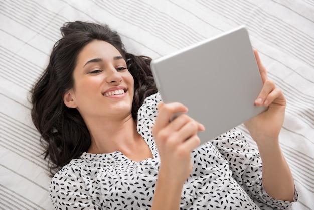 デジタルタブレットを使用してベッドに横たわって幸せな若い女性