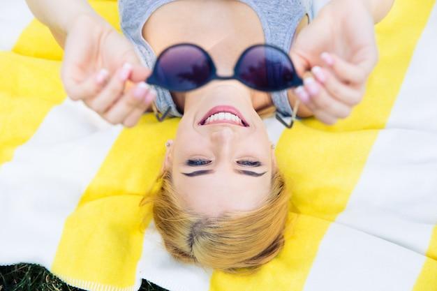 Счастливая молодая женщина, лежа на коврике