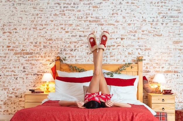 Счастливая молодая женщина, лежа на кровати с поднятыми ногами вверх
