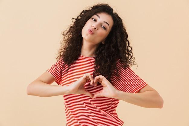 Счастливая молодая женщина делает жест любви сердца дуя поцелуи.
