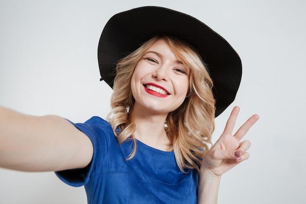 La giovane donna felice fa la posa del selfie