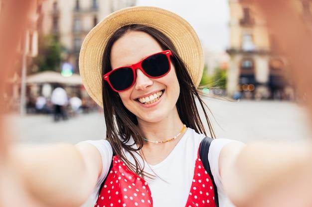 街の通りでスマートフォンで自分撮りを作る幸せな若い女性-バルセロナでの休暇中に楽しんでいる楽しい女性観光客-夏休みと幸せなライフスタイルのコンセプト