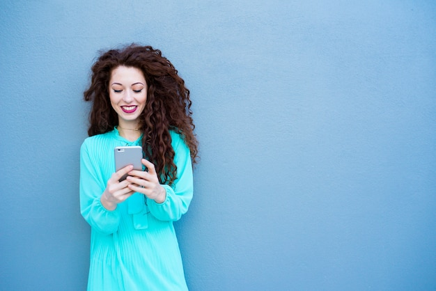 Happy young woman on the mobile phone on a blue wall