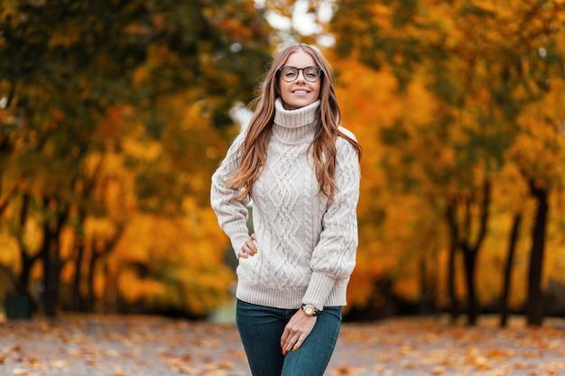 スタイリッシュなメガネの白いニットセーターを着た幸せな若い女性モデルが公園に立って、オレンジ色の葉と秋の木の背景に前向きに微笑んでいます。森の中のうれしそうな流行に敏感な女の子。
