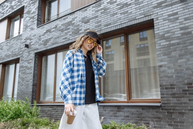 幸せな若い女性モデルは、コーヒーを飲みながら街の通りを歩きます。ライフスタイルファッションカタログのコンセプト。