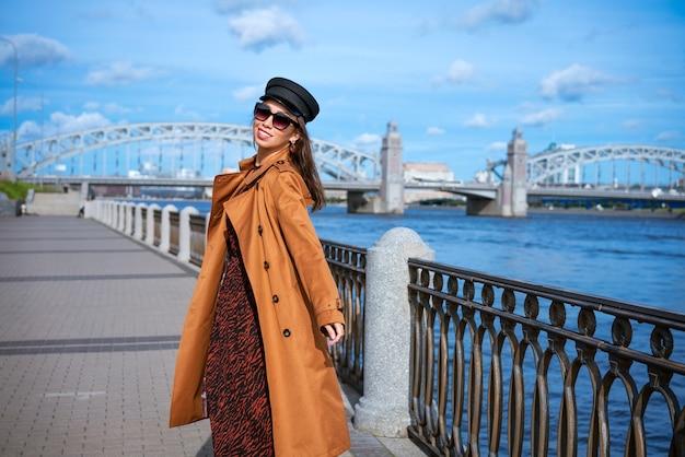 堤防でポーズをとって明るい茶色のコートと黒い帽子の白人民族の幸せな若い女性