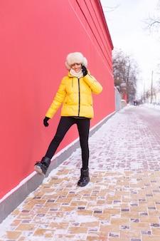 겨울 맑은 날에 따뜻한 옷을 입고 붉은 벽의 배경에 행복 한 젊은 여자 웃 고 눈 덮인 도시 보도에 전화로 이야기