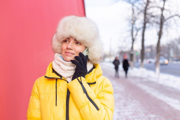 雪に覆われた街の歩道で笑顔と電話で話している冬の晴れた日に暖かい服を着て赤い壁の背景に幸せな若い女性