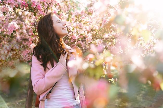 분홍색 사과 나무와 체리를 배경으로 눈을 감고 있는 행복한 젊은 여성
