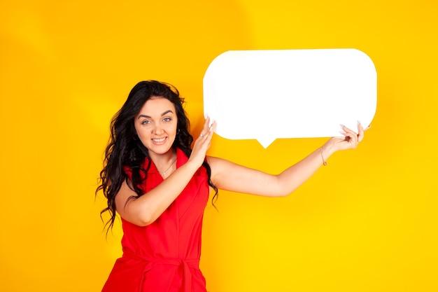 黄色の背景に幸せな若い女性。ブルネットのポートレート写真。テキスト用の空きスペースがある明るい黄色の背景。