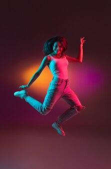 カジュアルなスタイルのネオンライト女性モデルのオレンジ色のスタジオの背景に幸せな若い女性