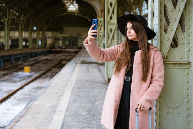 ピンクのコートと黒い帽子の駅のプラットホームで幸せな若い女性が電車を待っています...