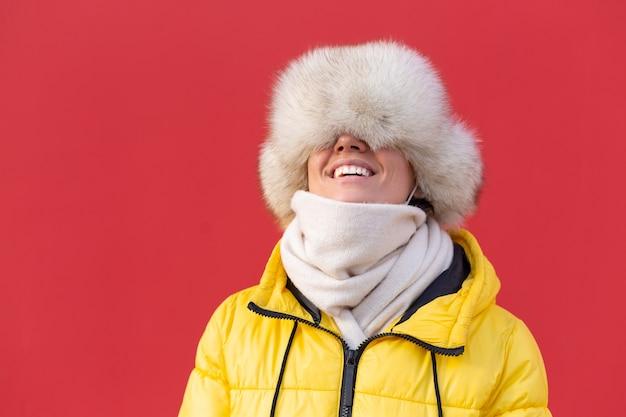 冬の晴れた日に暖かい服を着た赤い壁の背景に幸せな若い女性は真っ白な笑顔で微笑む