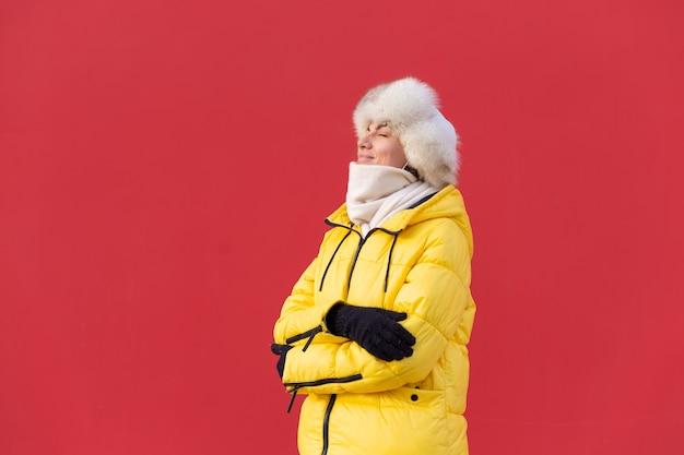 冬の晴れた日に暖かい服を着て赤い壁の背景に幸せな若い女性