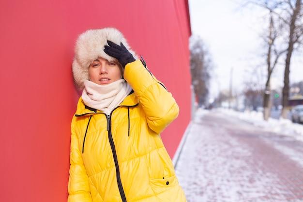 Счастливая молодая женщина на фоне красной стены в теплой одежде в зимний солнечный день