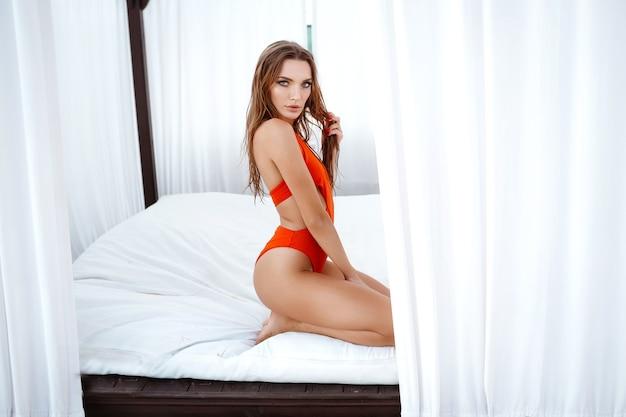 Счастливая молодая женщина на пляже. открытый модный портрет дамы очарования, наслаждающейся отдыхом на роскошной вилле в горячем тропическом острове. сексуальная идеально подходит женщина тела.
