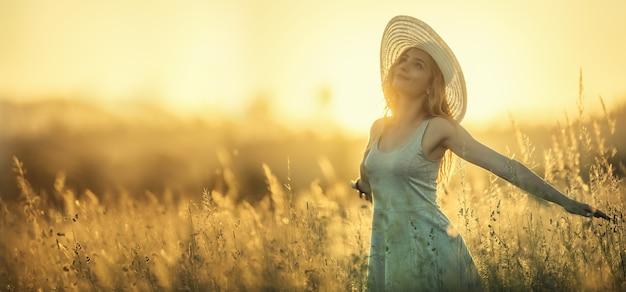 Счастливая молодая женщина на закате или восходе солнца в летней природе с открытыми руками.