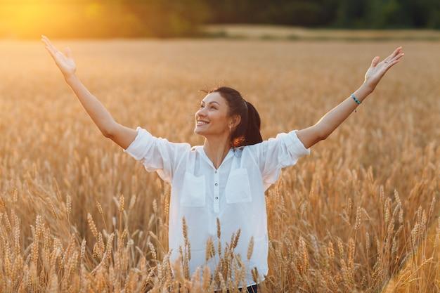 Счастливая молодая женщина на пшеничном поле с поднятыми вверх руками, наслаждаясь свободой