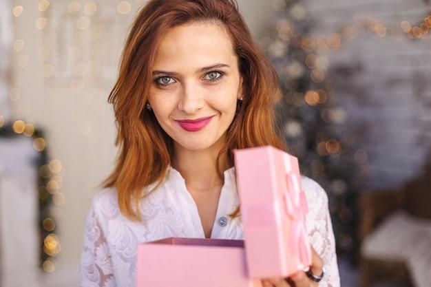 Счастливая молодая женщина раскрывая коробку подарка на рождество