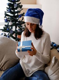 クリスマスプレゼントボックスを開く幸せな若い女性
