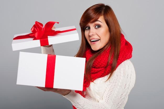 Счастливая молодая женщина открывает рождественский подарок