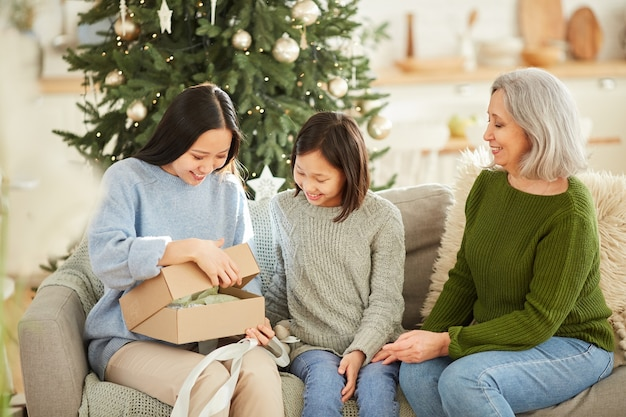 Happy young woman opening christmas present while sitting on sofa with her family at home
