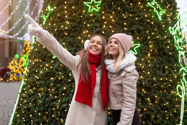 Happy young woman in outerwear pointing away for cheerful girlfriend while resting near christmas tree decorated with light garlands on street